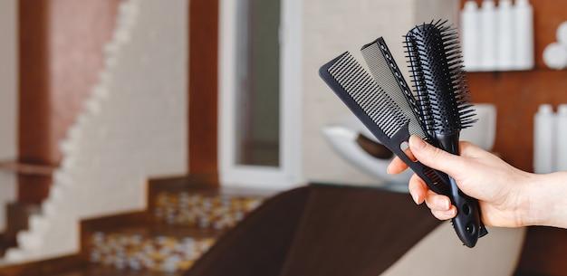 Pettini per capelli tagliati in mano femminile del parrucchiere contro la sedia del lavandino del lavaggio dei capelli all'interno del salone di bellezza.