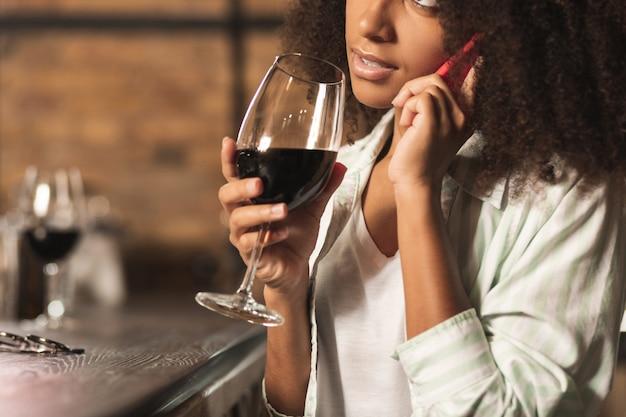 Venire. elegante giovane donna seduta al bancone del bar e bere vino mentre parla al telefono