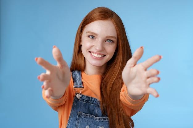 Vieni tra le braccia affascinante sincero felice gentile ragazza rossa baby sitter allungare le mani fotocamera voglio tenere fermo sorridente amichevole chiedendo passare oggetto in piedi sfondo blu raggiungere amico dare coccole