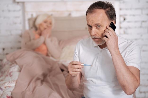 Vieni presto. uomo anziano preoccupato che tiene il termometro e chiama l'emergenza accanto alla moglie senior malata.