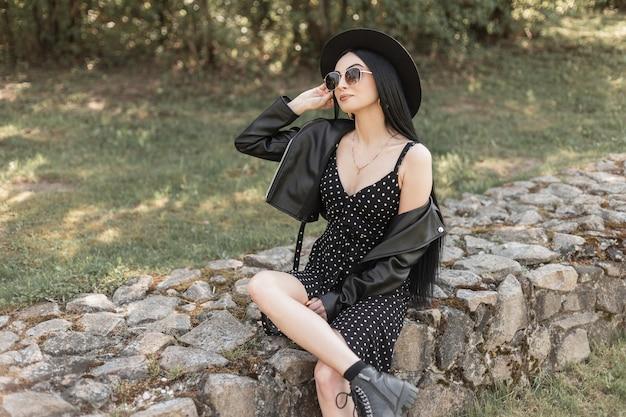 Bella giovane donna in occhiali da sole in bellissimo cappello in abiti casual primavera-estate neri alla moda della nuova collezione giovanile alla moda poggia su pietre sulla natura in una luminosa giornata di sole. modello di ragazza alla moda.