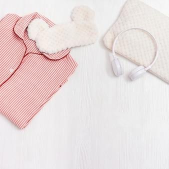 Comfort pigiama rosa, cuffie, cuscino, soffice maschera per dormire su superficie di legno bianca
