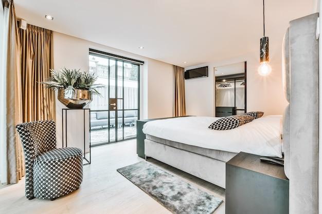 Comodo letto con coperta e cuscini situati vicino a lampade e sedia nella spaziosa camera da letto in appartamento moderno