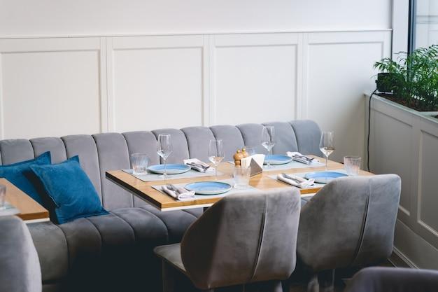 Comodo divano con cuscini, due sedie e tavolo in legno con piatti, tovaglioli, bicchieri e posate nell'accogliente caffetteria
