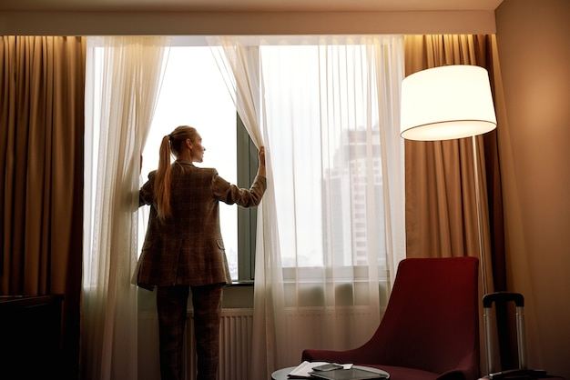 Confortevole camera d'albergo. la donna d'affari nella stanza d'albergo buia apre le tende alla finestra alla luce del mattino morning