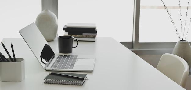 Stanza comoda dell'ufficio con il computer portatile e gli articoli per ufficio sulla tavola di legno bianca