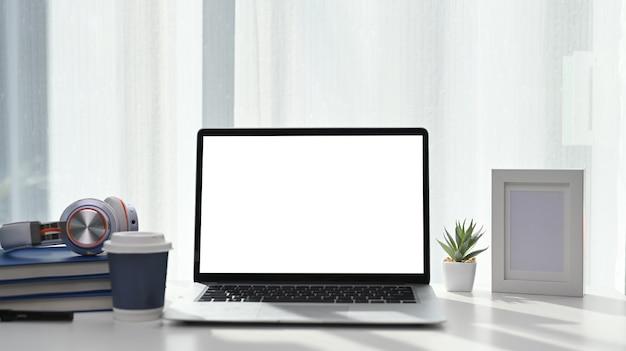 Posto di lavoro confortevole con computer portatile simulato con schermo vuoto, libri, cuffie e tazza di caffè.