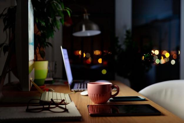 Spazio di lavoro comodo per lavoro a distanza a casa - tazza di tè, computer, laptop, lampada, tavoletta digitale, smartphone, pianta d'appartamento, taccuino, poltrona