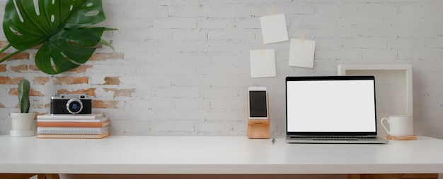 Area di lavoro confortevole con laptop, smartphone, decorazioni per la fotocamera e spazio di copia