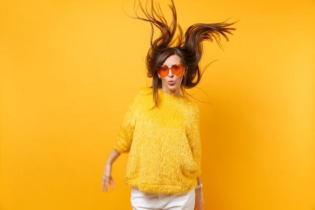 Comic giovane ragazza in maglione di pelliccia, occhiali cuore arancione scherzare in studio salto con capelli ventosi isolati su sfondo giallo brillante. persone sincere emozioni, concetto di stile di vita. zona pubblicità.