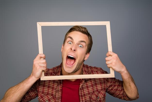 Giovane comico che mostra la lingua e che tiene la struttura di legno