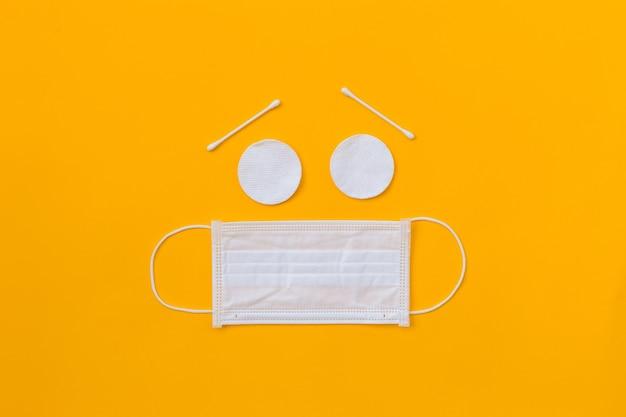 Tazza triste comica fatta di bastoncini di cotone, bastoncini e maschera chirurgica bianca su sfondo giallo. fermare il virus. pandemia di coronavirus. concetto di inquinamento atmosferico, banner piatto per bambini laici