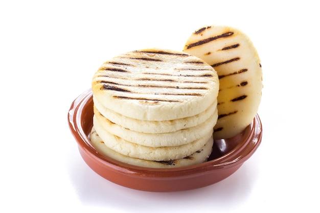 Comida tradicional venezolana, arepas en un fondo blanco.