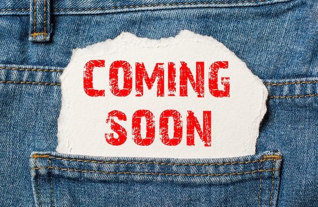 Prossimamente su carta bianca nella tasca dei jeans blu denim
