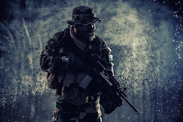 Combattente commando, mercenario professionista, soldato delle forze speciali con la faccia mimetizzata, carico di munizioni, fucile d'assalto armato, pattugliamento in missione segreta, furtivamente nell'oscurità pronto a combattere