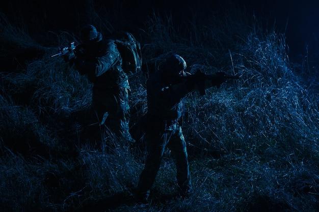 Gruppo di commando, gruppo tattico per operazioni speciali dell'esercito, squadra di pattuglia militare che marcia in campo carica di munizioni, si intrufola nell'oscurità, si muove con cautela e silenziosamente in linea durante la missione notturna