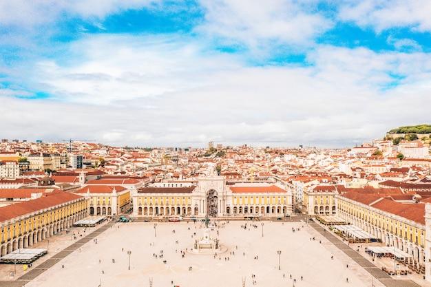 Piazza del commercio di lisbona con i turisti e i tetti arancioni degli edifici sotto il cielo nuvoloso