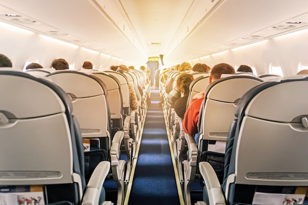 Cabina di aereo commerciale con file di sedili lungo il corridoio. luce del mattino nel salone dell'aereo di linea. classe economica
