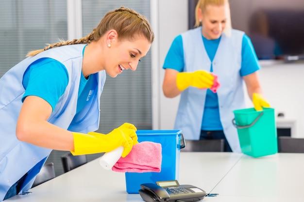 Signore dell'equipaggio di pulizia commerciale che lavorano come squadra in ufficio