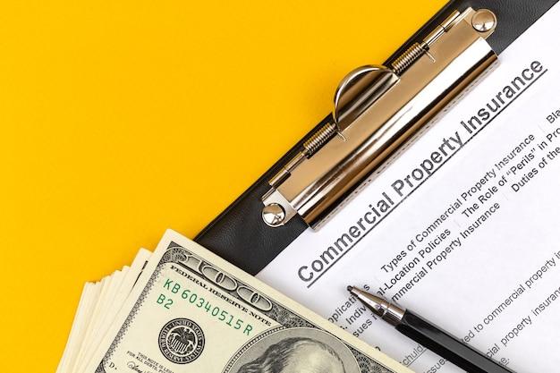 Modulo di assicurazione della proprietà commerciale. contratto di compravendita di beni immobili. appunti, dollari e penna su un desktop aziendale. foto vista dall'alto