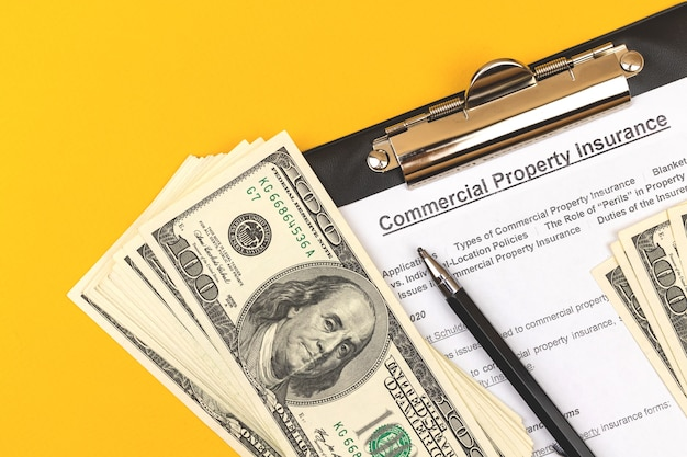 Modulo di assicurazione della proprietà commerciale. contratto e appalto di beni immobili. appunti con penna, dollari e penna su un desktop aziendale. foto vista dall'alto