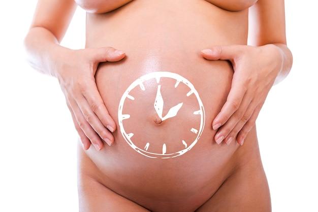 Presto in arrivo. primo piano della donna incinta che si tiene per mano sul suo addome con lo schizzo dell'orologio su di esso