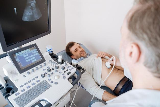 Professionista maturo impegnato che esamina lo stomaco dei pazienti utilizzando una tecnologia a ultrasuoni e osserva i risultati su uno schermo