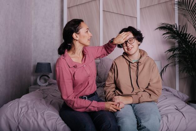 Comunicazione mamma bruna con figlia adolescente seduta sul letto in camera