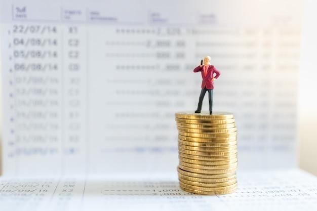 Comunicazione, affari, denaro e concetto finanziario. la figura in miniatura dell'uomo d'affari fa una telefonata sopra la pila di monete sul libretto di banca.