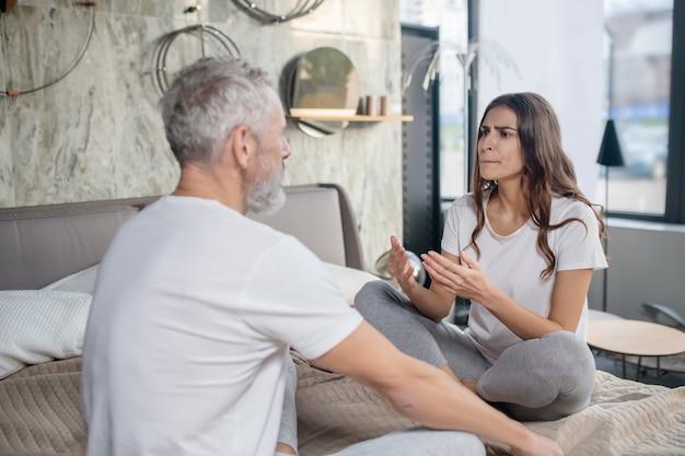 Comunicazione, complessità. convincente gesticola moglie che parla argomento e marito imperturbabile seduti uno di fronte all'altro a casa