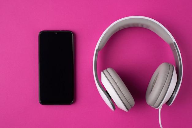Concetto di comunicazione. foto di vista dall'alto in alto di un telefono e cuffie isolati su sfondo rosa