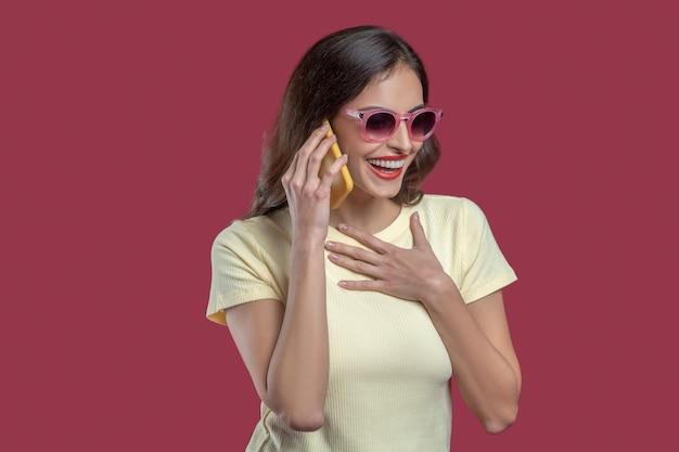 Comunicazione, gioia. emotiva gioiosa giovane donna in occhiali da sole parlando sullo smartphone gesticolando con la mano