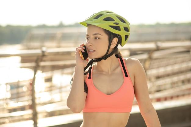 Comunicazione. una bella ragazza con un casco protettivo che parla al telefono