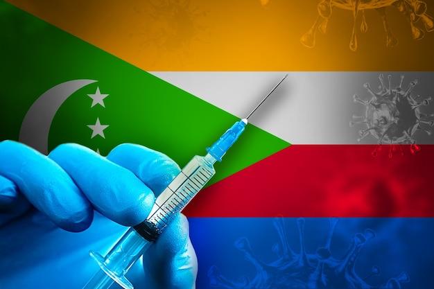 Comore covid19 campagna di vaccinazione la mano in un guanto di gomma blu tiene la siringa davanti alla bandiera