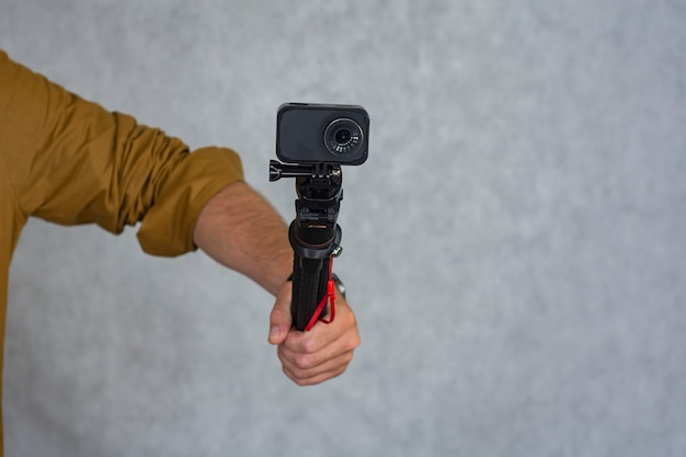 Action camera compatta su un treppiede flessibile in mano su uno sfondo chiaro.