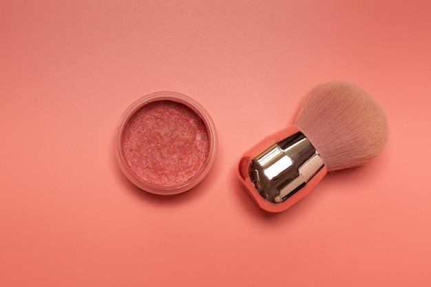 Fard compatto con pennello da trucco su sfondo rosa. primo piano