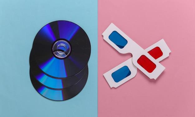Compact disc con occhiali stereo anaglifi su un pastello blu-rosa