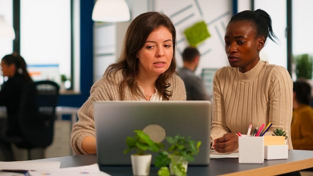 Direttore dell'azienda che spiega alla donna di colore i risultati del progetto apportando modifiche, lavorando davanti al laptop seduto alla scrivania nell'ufficio della società di avvio. concetto di lavoro di squadra e cooperazione