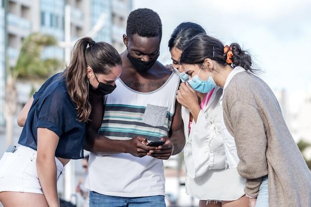 Compagnia di diversi amici che usano lo smartphone insieme in città