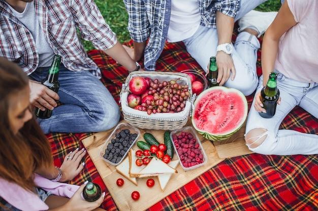La compagnia di quattro perdon con coperta, tappeto e cesto di frutta.