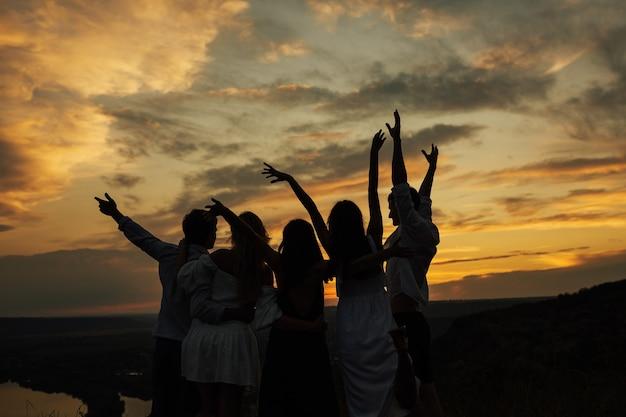 Compagnia di giovani amici al picnic al tramonto.