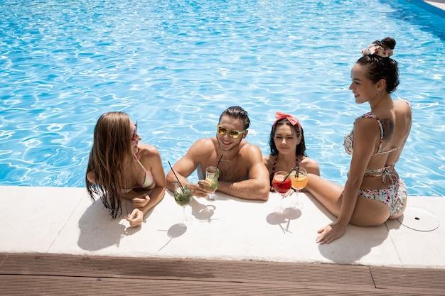 Compagnia di giovani ragazze e ragazzi allegri sono seduti sul bordo della piscina e bevono cocktail all'aria aperta in una soleggiata giornata estiva