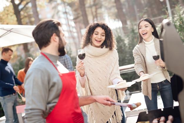 Una compagnia di giovani si è riunita per un barbecue.