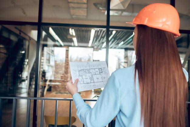 Confronto. donna dai capelli lunghi che guarda il piano di costruzione in piedi nel nuovo edificio di fronte alla parete di vetro nel pomeriggio