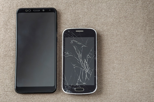 Confronto tra due telefoni cellulari neri, vecchio cellulare con schermo rotto e nuovo spazio moderno sul panno leggero. progresso della tecnologia e concetto di sostituzione.