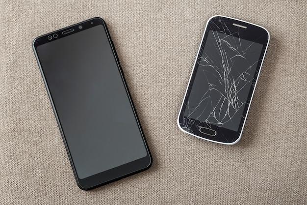 Confronto tra due telefoni cellulari neri, un vecchio cellulare con uno schermo rotto e uno nuovo e moderno. progresso della tecnologia e concetto di sostituzione.