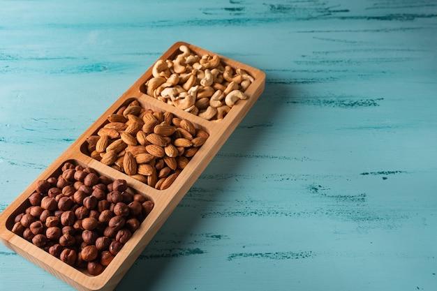 Piatto compartimentale con i dadi sulla tavola di legno blu. anacardi, nocciole, mandorle.