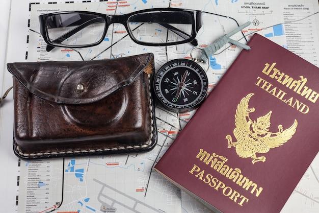 Bussola, macchina fotografica, passaporto, occhiali sulla mappa per i turisti