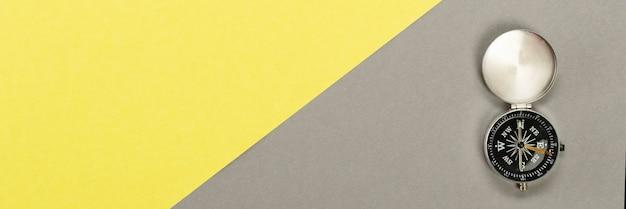 Bussola sulla superficie gialla grigia, concetto di viaggio minimo