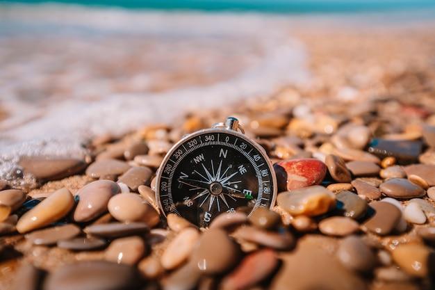 Bussola sdraiata su piccoli ciottoli della spiaggia con vista mare, concetto di viaggio